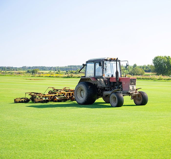 Tractor with a nozzle for care of a field lawn for a horse polo in work. The cut-off grass takes off from mechanical parts of a nozzle. Green flat field. Sky with beautiful clouds on background